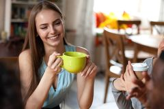 La donna attraente tiene la tazza di tè che si siede in caffè con gli amici immagine stock