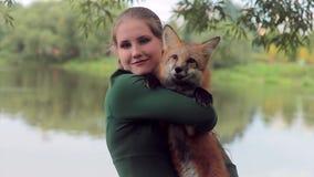 La donna attraente tiene la volpe arancio, stante sulla sponda del fiume all'aperto video d archivio