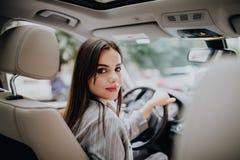 La donna in automobile dell'interno tiene la ruota girare intorno sorridere esaminando i passeggeri in tassista di idea del sedil fotografia stock libera da diritti