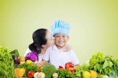 La donna bacia suo figlio con la verdura sulla tavola Immagini Stock