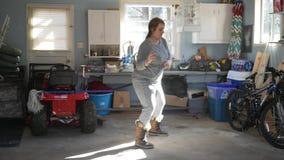 La donna balla in un garage a musica dopo pulizie di primavera stock footage