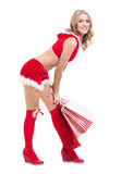 La donna beautyful felice nel Babbo Natale rosso copre con i sacchetti della spesa Fotografia Stock Libera da Diritti