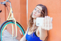 La donna bella dei pantaloni a vita bassa fa il selfie di se stessa vicino alla bicicletta d'annata Fotografia Stock