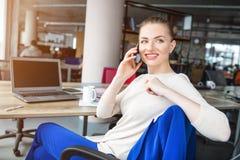 La donna bella e felice sta sedendosi nella sedia e nella conversazione Il Se sta guardando da parte e sorridere La ragazza ha do fotografie stock