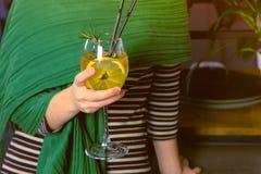 La donna beve il cocktail dell'alcool in caffè Passa il primo piano immagini stock
