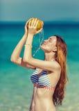 La donna beve il succo della noce di cocco, fuoco molle Fotografia Stock