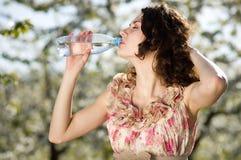 La donna beve l'acqua fredda in il giardino di primavera Fotografie Stock Libere da Diritti