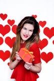 La donna bianca con le labbra rosse che danno un regalo su cuore ha modellato il fondo Giorno del `s del biglietto di S Fotografie Stock Libere da Diritti