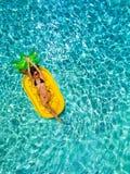 La donna in bikini si rilassa su un galleggiante a forma di ananas in uno stagno immagini stock libere da diritti