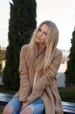La donna bionda abbastanza alla moda dei giovani si è vestita in jeans strappati e maglione bianco Fotografie Stock