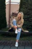 La donna bionda abbastanza alla moda dei giovani si è vestita in jeans strappati e maglione bianco Immagini Stock Libere da Diritti