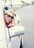 La donna bionda abbastanza giovane guarda fuori dalla finestra di automobile Immagine Stock