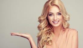 La donna bionda con capelli ricci dimostra il vostro prodotto Immagini Stock