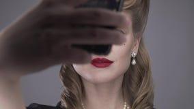 La donna bionda con gli occhi azzurri e la retro acconciatura sta prendendo i selfies, 4k video d archivio