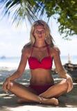La donna bionda in costume da bagno rosso si siede alla spiaggia tropicale immagini stock