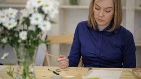 La donna bionda crea lo schizzo sul pezzo spesso di cartone in officina archivi video