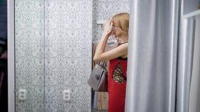 La donna bionda di Beautifuil entra in spogliatoio in un boutique archivi video