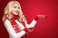 La donna bionda di risata felice si è vestita nel Natale dura con i pollici su, su fondo rosso ha spazio della copia Fotografia Stock