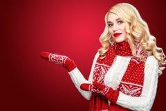 La donna bionda di risata felice si è vestita nel Natale dura con i pollici su, su fondo rosso ha spazio della copia Immagine Stock