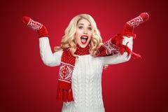 La donna bionda di risata felice si è vestita nel Natale dura con i pollici su, su fondo rosso ha spazio della copia Fotografie Stock Libere da Diritti