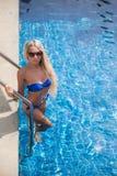 La donna bionda esile ottiene l'abbronzatura vicino alla piscina fotografie stock libere da diritti