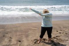 La donna bionda fa un movimento tamponante di ballo sulla spiaggia immagine stock