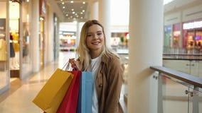 La donna bionda felice esamina i suoi sacchi di carta variopinti che stanno nel centro commerciale video d archivio