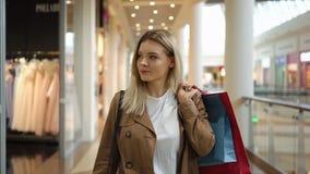 La donna bionda felice sorride camminando con i sacchetti della spesa intorno al centro commerciale stock footage