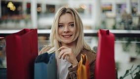 La donna bionda felice sta dietro i sacchetti della spesa variopinti nel centro commerciale stock footage