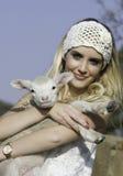 La donna bionda graziosa con bianco lavora all'uncinetto la fascia che tiene il piccolo agnello Fotografia Stock Libera da Diritti