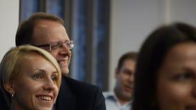 La donna bionda graziosa sorridente ascolta la conferenza interessante