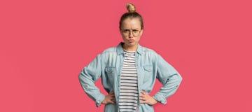 La donna bionda infelice sta in una posa con il fronte serio fotografia stock