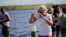 La donna bionda matura prende le foto sul fiume vicino della videocamera dello smartphone video d archivio