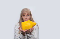La donna bionda mostra il monebox giallo del maiale Fotografia Stock Libera da Diritti