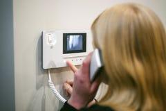 La donna bionda risponde alla chiamata del citofono Fotografie Stock Libere da Diritti