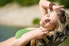 La donna bionda si distende in bikini nel lago fotografia stock