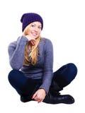 La donna bionda sorridente in inverno copre sopra bianco Fotografie Stock