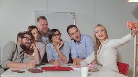 La donna bionda sta prendendo il selfie con i suoi colleghi in ufficio, facendo uso degli smartphones archivi video