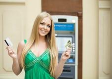 La donna bionda in un vestito verde sta tenendo i dollari dei contanti Immagini Stock Libere da Diritti