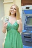 La donna bionda in un vestito verde sta tenendo i dollari dei contanti Fotografie Stock Libere da Diritti