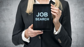 La donna bionda in vestito convenzionale presenta una compressa con le parole 'Job Search' sullo schermo Un concetto del processo Immagini Stock Libere da Diritti