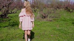 La donna bionda in vestito rosa cammina da un giardino di fioritura con gli alberi stock footage