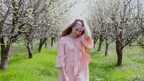 La donna bionda in vestito rosa cammina da un giardino di fioritura con gli alberi archivi video