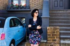 La donna in blu ha fiorito il vestito, gli occhiali da sole ed il cappello Fotografia Stock