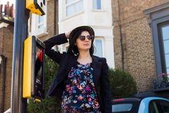 La donna in blu ha fiorito il vestito, gli occhiali da sole ed il cappello Fotografie Stock
