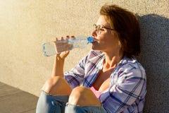 La donna in buona salute adulta beve l'acqua dalla bottiglia Fotografia Stock Libera da Diritti