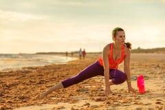 La donna in buona salute di misura negli sport innesta sull'allungamento del litorale Immagine Stock
