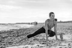 La donna in buona salute di misura negli sport innesta sull'allungamento del litorale Fotografia Stock Libera da Diritti