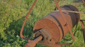 La donna cade la catena con il secchio nel pozzo rustico per estrarre l'acqua stock footage