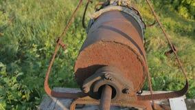 La donna cade la catena con il secchio nel pozzo rustico per estrarre l'acqua Fine d'annata della catena del pozzo d'acqua su Vec video d archivio